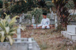 Gambaran seorang anak di atas makam orang tuanya
