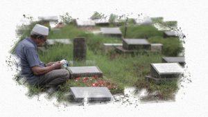 Salah seorang anggota keluarga sedang berziarah ke kuburan keluarganya